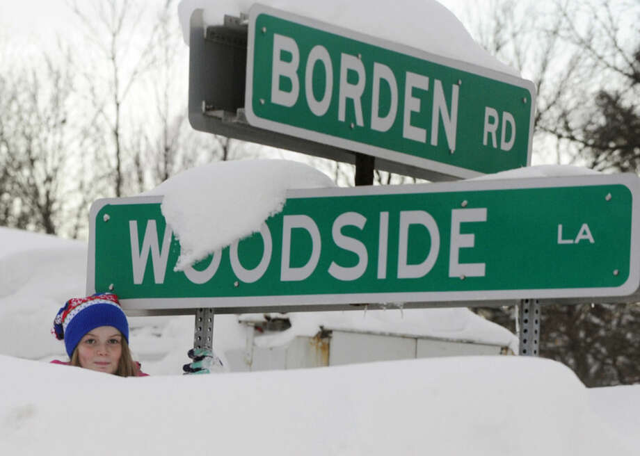 Annabella Hopkins peeks over a snowbank piled high at this intersection in Cheektowaga, N.Y., Thursday, Nov. 20, 2014. The corner of Borden Rd. and Woodside has been a staging ground for National News media outlets filing reports on storms that have dumped more than 5 feet of snow on western New York. (AP Photo/Gary Wiepert)