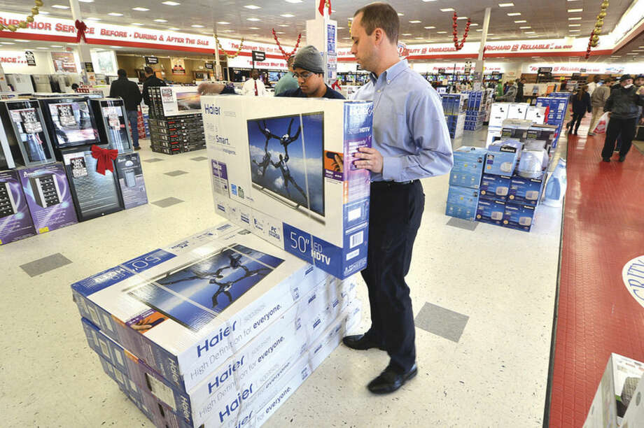 Hour Photo/Alex von Kleydorff P.C.Richard and Son Store Manager Robert Krynski helps to set out some TV's for Black Friday sales at the Connecticut Ave. store on Friday