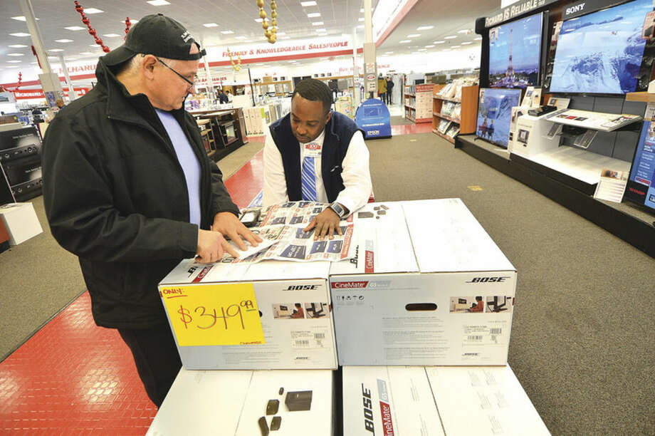 Hour Photo/Alex von Kleydorff Nicholas DiFilipo goes over some options with Sales Counselor Mark Murray while shopping for a big screen HDTV during Black Friday sales event at P.C. Richard and Son on Connecticut Ave