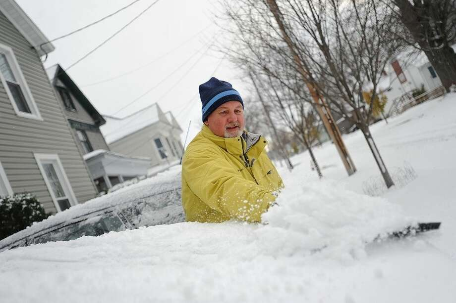 In a Tuesday, Nov. 18, 2014 photo, Brian F. Miller clears snow off his wife's car on Boyd Street in Watertown, N.Y. Before he finished his wife announced from the porch that she didn't have to go to work at the Jefferson County Courthouse due to weather. A ferocious lake-effect storm left the Buffalo area buried under 6 feet of snow, trapping people on highways and in homes, and another storm expected to drop 2 to 3 feet more was on its way. (AP Photo/The Watertown Daily Times, Justin Sorensen) SYRACUSE OUT