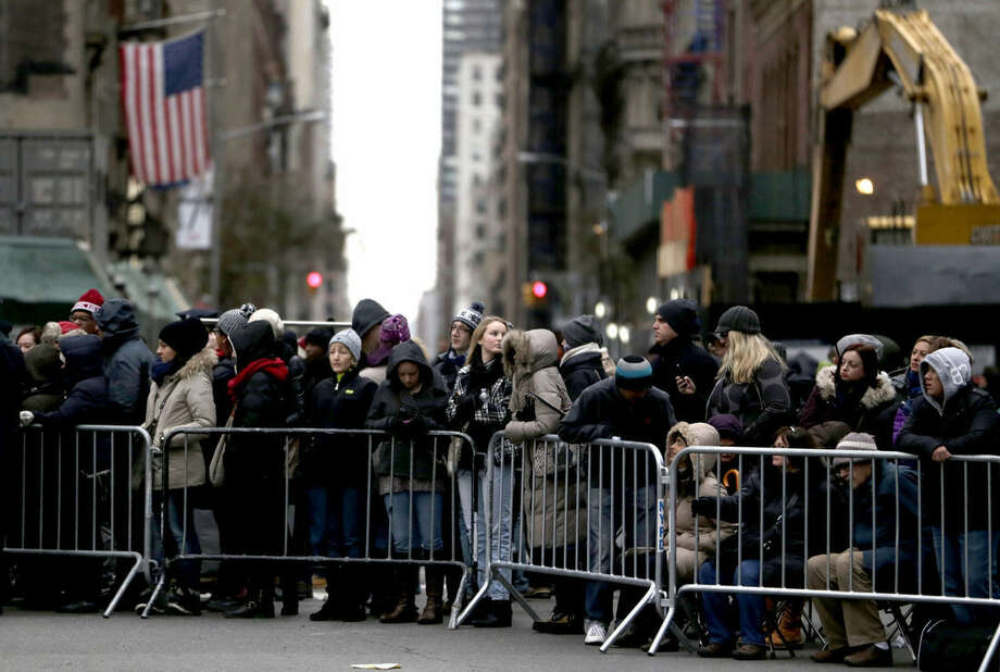 People wait for the start of the Macy's Thanksgiving Day Parade, Thursday, Nov. 27, 2014, in New York. (AP Photo/Julio Cortez)