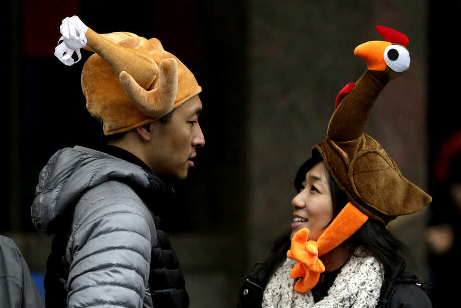 Tamari Hedani, right, and her boyfriend, Chris Chu, both from San Francisco, wear turkey hats prior to the start of the Macy's Thanksgiving Day Parade, Thursday, Nov. 27, 2014, in New York. (AP Photo/Julio Cortez)