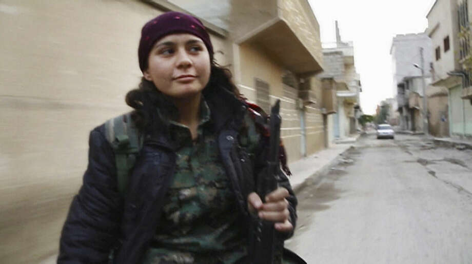 In this image made from a video taken in late November, 2014, Kurdish fighter Pervin Kobani rides in the back of a pickup truck through Kobani, Syria. On the front lines of the battle for Kobani, Kurdish female fighters have been playing a major role in helping defend the Syrian town from an onslaught by the Islamic State extremist group. Pervin Kobani is one of them. She is 19 years old, a farmer's daughter. In late November, she was part of a team holding an eastern frontline position coming under regular attack from extremist fighters trying to take the town since mid-September. (AP Photo/Jake Somkin via AP video)