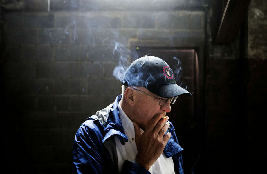 "In this Oct. 15, 2014 photo, coal mine owner C.V. Bennett III, smokes a cigarette while walking through an abandoned coal power plant in Lynch, Ky. Bennett's family has been mining in Harlan County since 1912. In the last few years, Bennett's work force has dropped from more than 600 to fewer than 200.""That hurts me more than anything else, is seeing people I've known and grown up with,"" he says. ""To have a future and then all of a sudden to have that future jerked out from underneath them, with no hope of it ever coming back."" (AP Photo/David Goldman)"