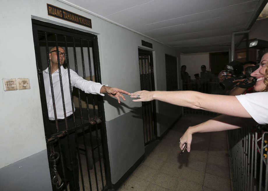 In this Tuesday, Dec. 2, 2014 photo, Canadian teacher Neil Bantleman, left, reaches out to his wife Tracy from inside a holding cell prior to the start of his trial hearing at South Jakarta District Court in Jakarta, Indonesia. Bantleman and an Indonesia teaching assistant, Ferdinant Tjiong, went on trial Tuesday on accusation of sexually abusing a kindergartner on the campus of a prestigious international school in the capital. (AP Photo/Tatan Syuflana)