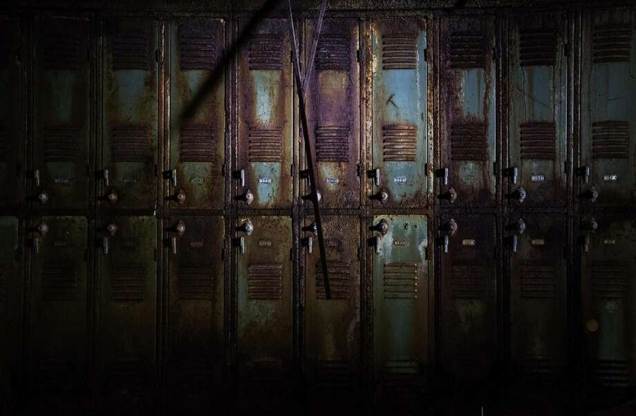 In this Oct. 17, 2014 photo, rusted lockers stand in a dark hallway of the abandoned Lynch High School in Lynch, Ky. As Harlan County's population shrunk along with the coal industry, the school closed in 1981. The county consolidated districts and now school stands abandoned up the street from the old mines. (AP Photo/David Goldman)