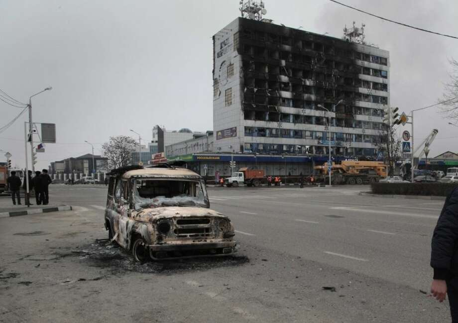 People pass a burned police car outside a burned-out publishing house in central Grozny, Russia, Thursday, Dec. 4, 2014. A gun battle broke out early Thursday in the capital of Russia's North Caucasus republic of Chechnya, puncturing the patina of stability ensured by years of heavy-handed rule by a Kremlin-appointed leader. The violence erupted hours before Russian President Vladimir Putin began his annual state of the nation address in Moscow.(AP Photo/Musa Sadulayev)