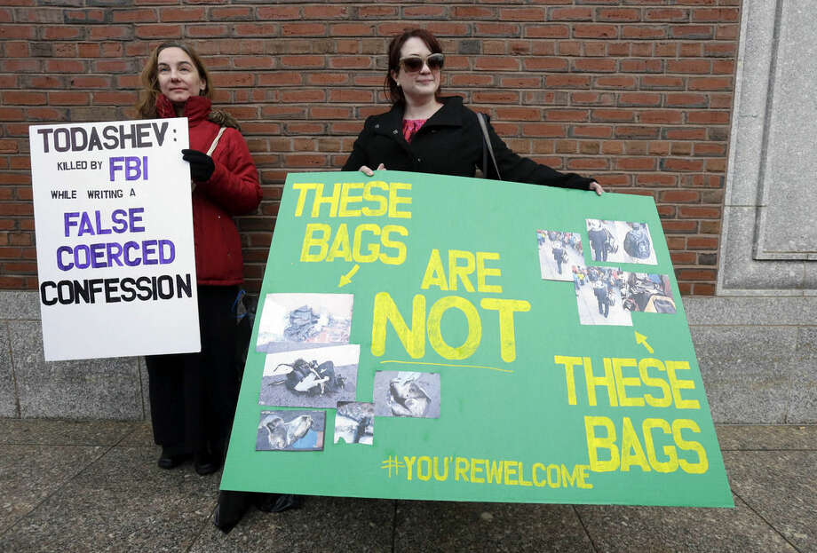 Protestors hold signs outside federal court in Boston Thursday, Dec. 18, 2014, where Boston Marathon bombing suspect Dzhokhar Tsarnaev is scheduled for a final hearing before his trial begins in January. Tsarnaev is charged with the April 2013 attack that killed three people and injured more than 260. He could face the death penalty if convicted. (AP Photo/Steven Senne)