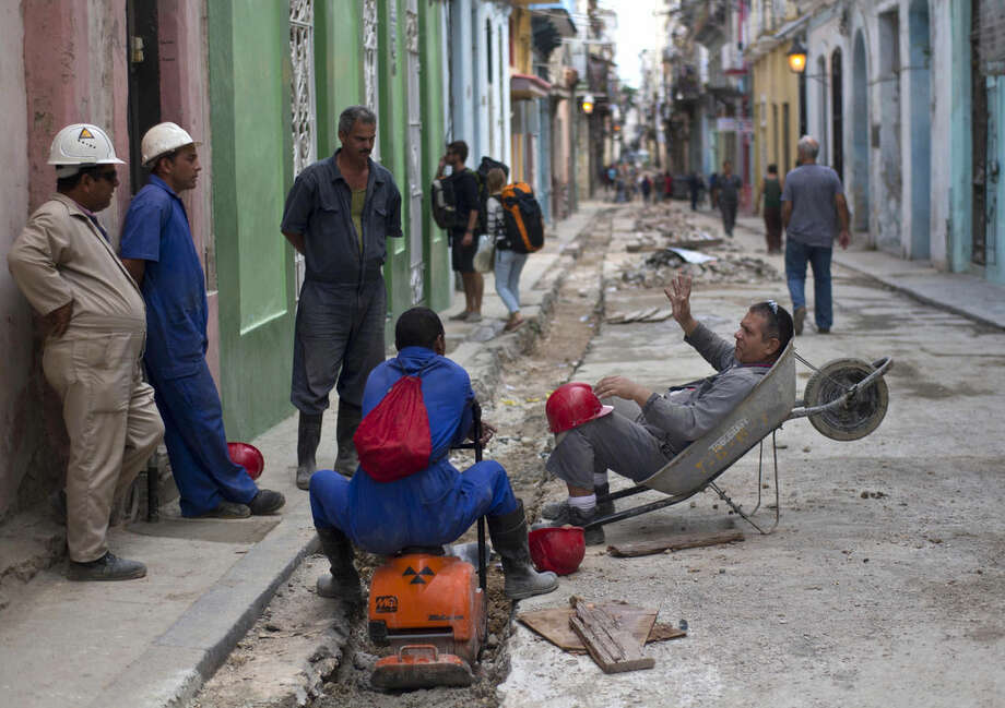 """Construction workers speculate what Cuba's President Raul Castro will announce in an upcoming live, nationally broadcast speech in Havana, Cuba, Wednesday, Dec. 17, 2014. Castro spoke about the country's restoration of relations with the United States, saying that profound differences remain between Cuba and the U.S. in areas such as human rights, foreign policy and questions of sovereignty, but that the countries have to learn to live with their differences """"in a civilized manner."""" (AP Photo/Ramon Espinosa)"""