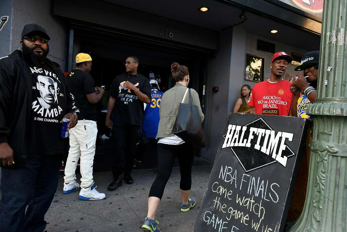 Fans stand outside Halftime Sports Bar during game five of the NBA championship between the Golden State Warriors and the Cleveland Cavaliers on Monday, June 13, 2016, in Oakland, Calif.