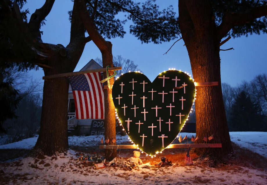 FILE - In this Dec. 14, 2013 file photo, a makeshift memorial with crosses for the victims of the Sandy Hook Elementary School shooting massacre stands outside a home in Newtown, Conn., on the one-year anniversary of the shootings. Newtown is taking its time to decide what a permanent memorial should look like. A commission has been hearing proposals for concepts including murals, groves and memorial parks, while looking for lessons from paths chosen by other tragedy-stricken communities. Public forums are planned for 2015, the next step in a process that is expected to last several more years. (AP Photo/Robert F. Bukaty, File)