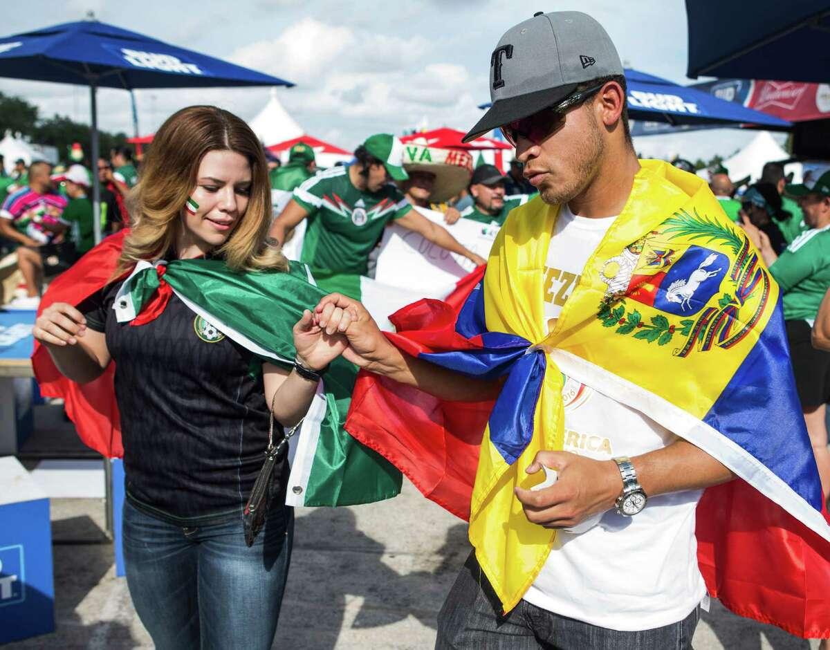 Mexico fan Alison Sifuentes, left, and Venezuela fan Carlos Paredes Aldana wear their colors Monday outside NRG Stadium before their teams meet.