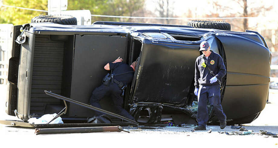 A police officer checks Carolina Panthers NFL football quarterback Cam Newton's truck following a two-vehicle crash not far from the team's stadium in Charlotte, N.C., Tuesday, Dec. 9, 2014. Television footage showed Newton on a stretcher being placed in an ambulance. It was unclear how badly the 25-year-old was injured. (AP Photo/The Charlotte Observer, Todd Sumlin) MAGS OUT; TV OUT; NEWSPAPER INTERNET ONLY