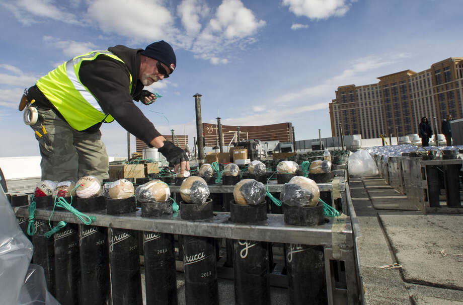 Pyrotechnician Henry Herman loads aerial shells during New Years Eve fireworks preparation on the roof of the Treasure Island hotel-casino in Las Vegas, Tuesday, Dec. 30, 2014. The Fireworks by Grucci show will explode from the rooftops of seven casinos. (AP Photo/Las Vegas Sun, Steve Marcus)