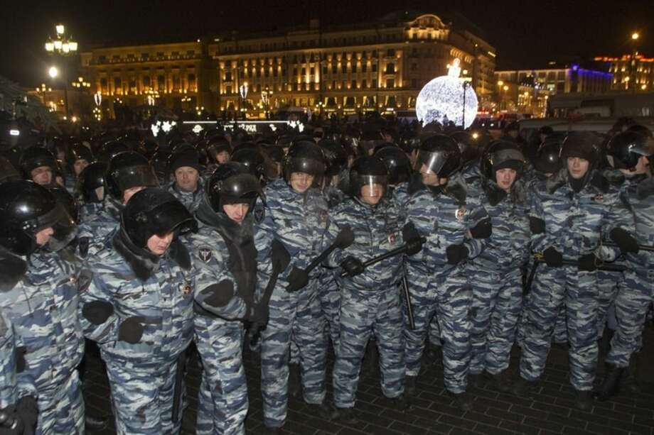 Police prepare to push supporters of Russian opposition activist and anti-corruption crusader Alexei Navalny away during an unsanctioned protest in Manezhnaya Square in Moscow, Russia, Tuesday, Dec. 30, 2014. The unsanctioned protest came hours after Alexei Navalny was found guilty of fraud and given a suspended sentence. Navalny, who has been under house arrest since February, is accused of breaking the terms of his house arrest to attend the rally and was detained by police as he approached the site of the protest. (AP Photo/Denis Tyrin)