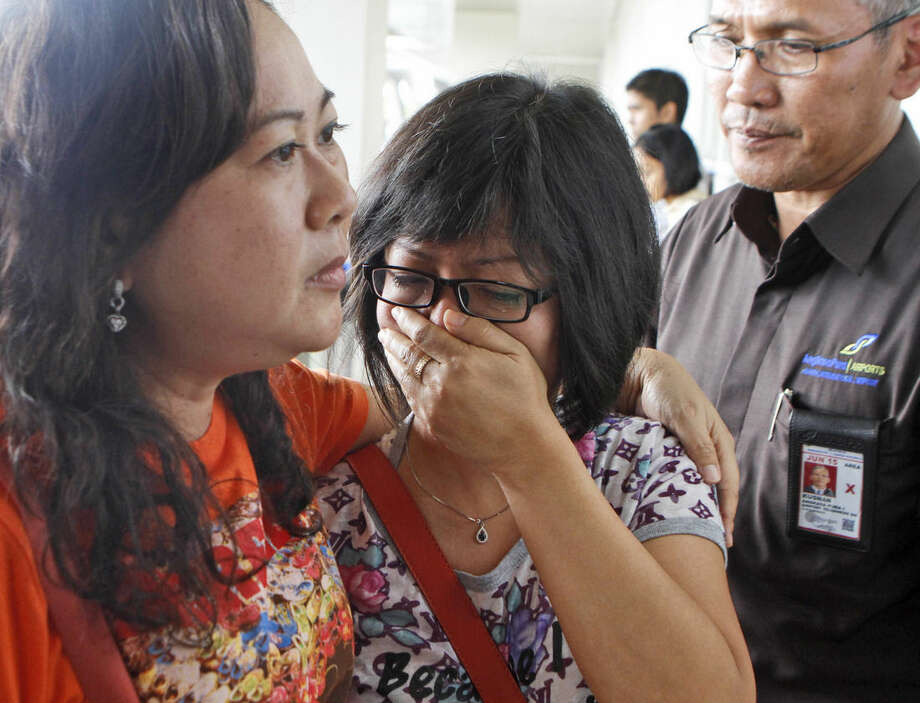 A relative of AirAsia flight QZ8501 passengers weeps as she waits for the latest news on the missing jetliner at Juanda International Airport in Surabaya, East Java, Indonesia, Sunday, Dec. 28, 2014. A massive sea search was underway for the AirAsia plane that disappeared Sunday while flying from Indonesia to Singapore through airspace possibly thick with dense storm clouds, strong winds and lightning, officials said. (AP Photo/Trisnadi)