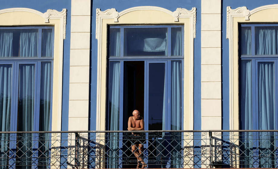 In this Dec. 19, 2014 photo, a tourist looks out from his hotel room's balcony in Havana, Cuba. In the past, people-to-people U.S. travelers could only go to Cuba under a license obtained by a travel company in a time-consuming process followed by lengthy government verification that travelers weren't engaging in inappropriate leisure tourism. (AP Photo/Desmond Boylan)