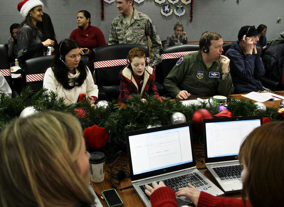 "FILE - In this Dec. 24, 2012 file photo, U.S. Air Force Brig. Gen. Richard Scobie, right, his son Andrew, center, and wife, Janis, all take phone calls from children asking where Santa is and when he will deliver presents to their house, during the annual NORAD Tracks Santa Operation, at the North American Aerospace Defense Command, or NORAD, at Peterson Air Force Base, Colo. Santa is poised for another monster year on social media. NORAD Tracks Santa has already attracted a record 1.49 million Facebook ""likes"" before the journey even begins. And for Christmas Eve 2014, there's a website version for smartphones. (AP Photo/Brennan Linsley, File)"