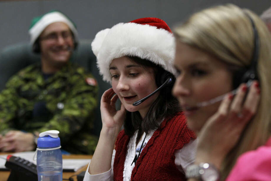 "FILE - In this Dec. 24, 2012, file photo, volunteer Katherine Beaupre takes phone calls from children asking where Santa is and when he will deliver presents to their house, during the annual NORAD Tracks Santa Operation, at the North American Aerospace Defense Command, or NORAD, at Peterson Air Force Base, in Colorado Springs, Colo. Santa is poised for another monster year on social media. NORAD Tracks Santa has already attracted a record 1.49 million Facebook ""likes"" before the journey even begins. And for Christmas Eve 2014, there's a website version for smartphones. (AP Photo/Brennan Linsley, File)"