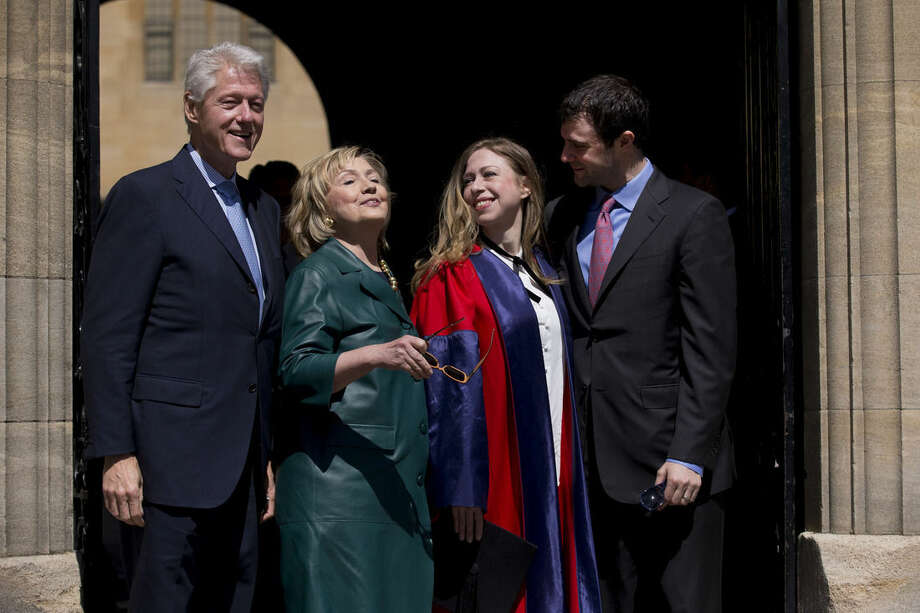 FILE - This, May 10, 2014, file photo, shows Former U.S. Secretary of State Hillary Rodham Clinton, second left, as she takes off her sunglasses to pose for a group photograph with her husband former U.S. President Bill Clinton, left, their daughter Chelsea, second right, and her husband Marc Mezvinsky, as they leave after they all attended Chelsea's Oxford University graduation ceremony at the Sheldonian Theatre in Oxford, England. Again? Really? There are more than 300 million people in America, yet the same two families keep popping up when it comes to picking a president. The possibility of a Bush-Clinton matchup in 2016 is increasingly plausible. After months of hints and speculation, former Florida Gov. Jeb Bush last week said he's actively exploring a bid for the Republican nomination. And while Hillary Rodham Clinton hasn't revealed her intentions, she's seen as the odds-on favorite for the Democratic nomination. (AP Photo/Matt Dunham, File)