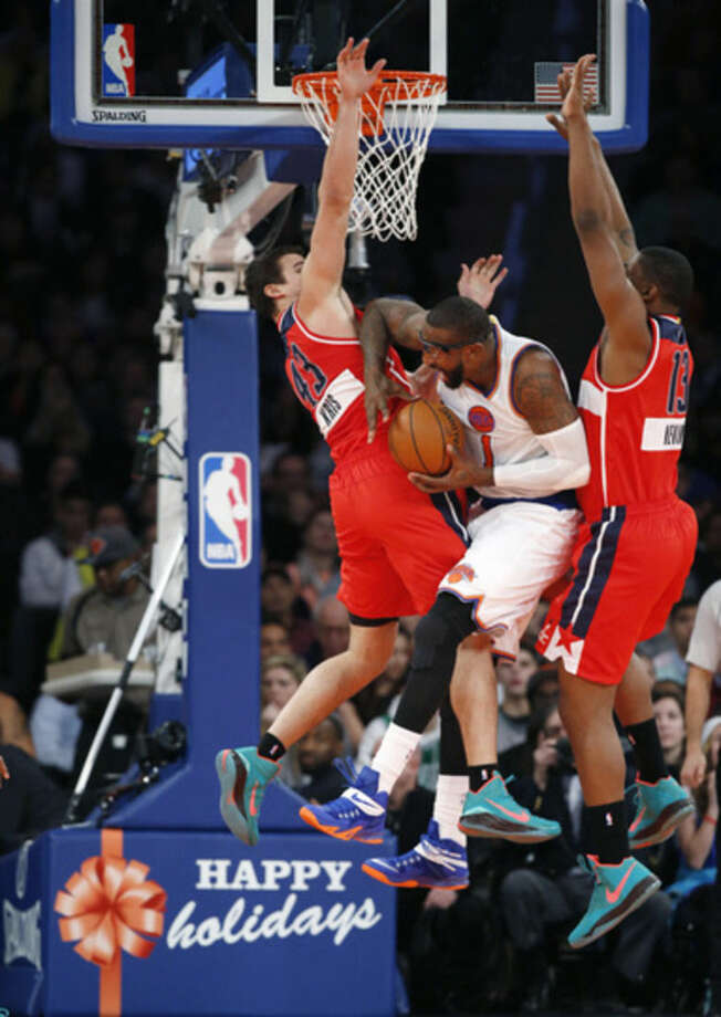 Washington Wizards forward Kris Humphries (43) and Wizards center Kevin Seraphin (13) sandwich New York Knicks forward Amar'e Stoudemire (1) between them as he goes up for a layup in the first half of an NBA basketball game at Madison Square Garden in New York, Thursday, Dec. 25, 2014. (AP Photo/Kathy Willens)