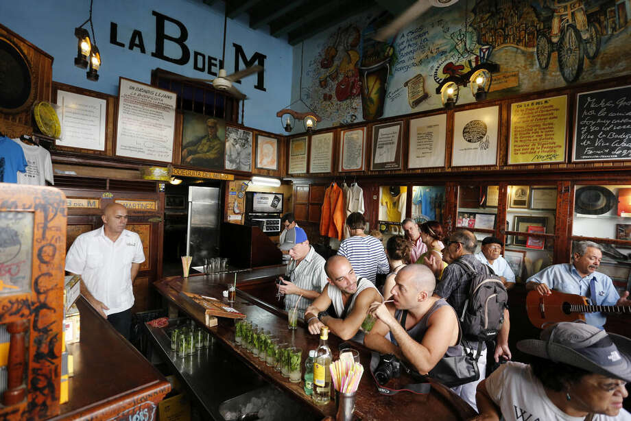 In this Dec. 19, 2014 photo, tourists fill the famous La Bodeguita del Medio bar where U.S. author Ernest Hemingway used to drink in Old Havana, Cuba. Experts don't expect American tourists to flood Cuba soon after new travel regulations are established, guzzling mojitos and lining up at beachside buffets. The complexity of the legal details and the possibility, even remote, of fines for violations will probably mean most new travel to Cuba will still go through tour organizers. (AP Photo/Desmond Boylan)