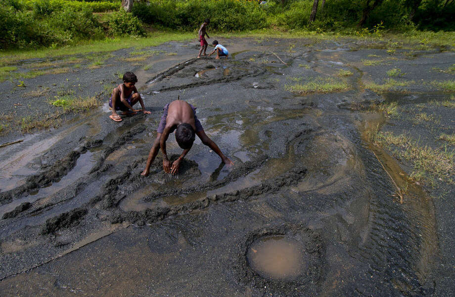 In this Sept. 13, 2014 photo, children play on a farmland destroyed by asbestos sediments in Roro, India. An asbestos mine, abandoned nearly three decades ago still affects the people around it and 18 were diagnosed with asbestosis in 2012. Tens of thousands more, some former mine workers, remain untested and at risk. (AP Photo/Saurabh Das)