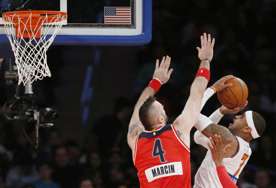 Washington Wizards center Marcin Gortat (4) defends New York Knicks forward Carmelo Anthony (7) in the first half of an NBA basketball game at Madison Square Garden in New York, Thursday, Dec. 25, 2014. (AP Photo/Kathy Willens)