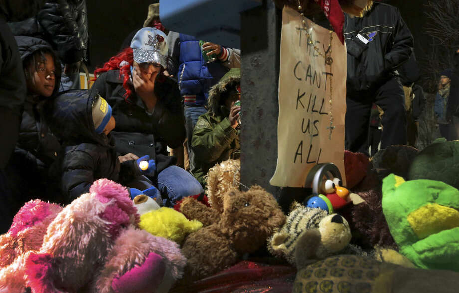 Courtney Palmer, center left, a cousin of Antonio Martin, mourns the loss at a growing memorial in a gas station parking lot in Berkeley, Mo., Wednesday, Dec. 24, 2014. The mayor of the St. Louis suburb of Berkeley urged calm Wednesday after a white police officer killed the black 18-year-old who police said pointed a gun at him, reigniting tensions that have lingered since the death of Michael Brown in neighboring Ferguson. (AP Photo/St. Louis Post-Dispatch, Robert Cohen)