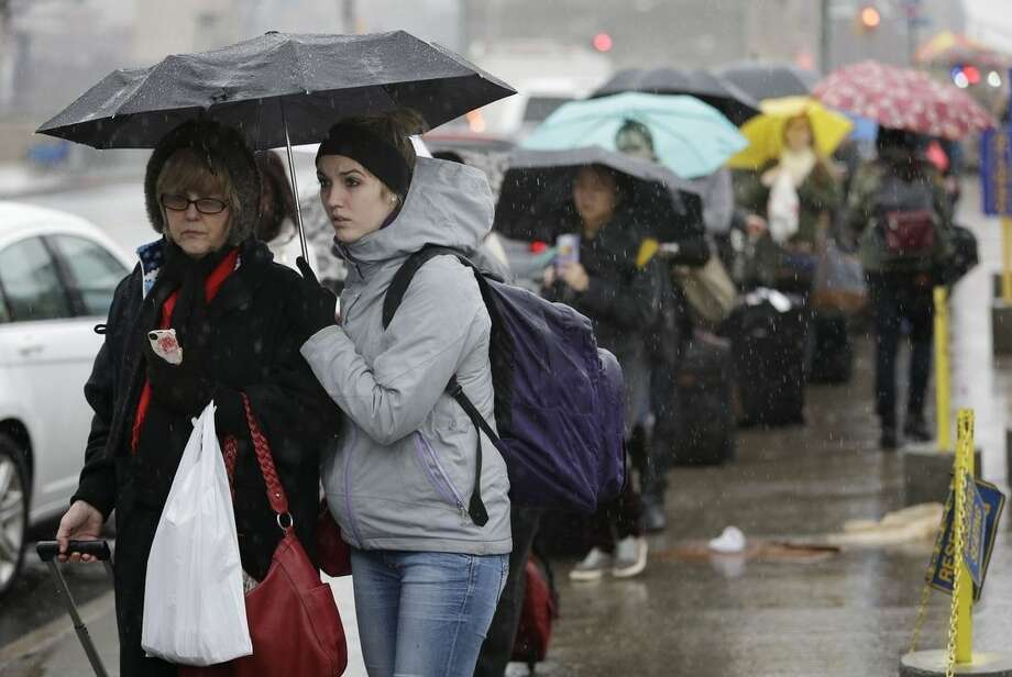 Travelers wait in the rain to board a bus for Washington, D.C. in New York, Wednesday, Dec. 24, 2014. Christmas Eve is shaping up to be windy, wet and warm instead of white across much of the country. (AP Photo/Seth Wenig)