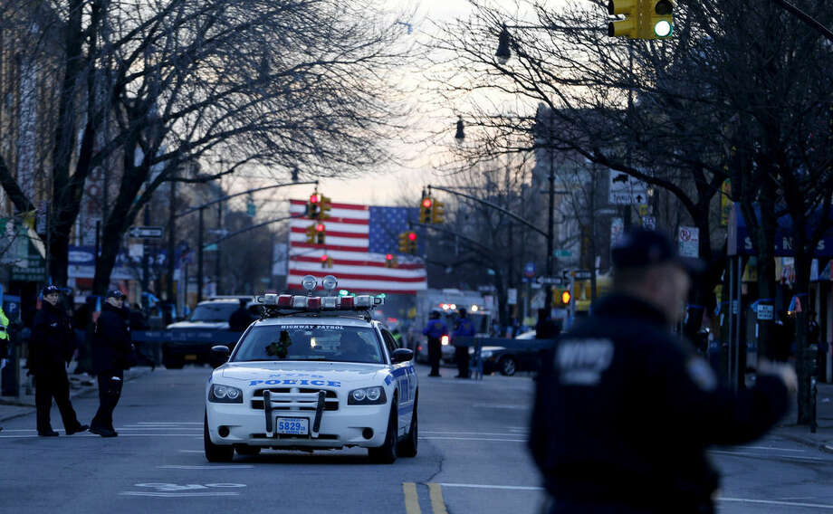 A New York Police Department vehicle cruises toward Christ Tabernacle Church before funeral services for officer Rafael Ramos at in the Glendale section of Queens, Saturday, Dec. 27, 2014, in New York. Ramos and his partner, officer Wenjian Liu, were killed Dec. 20 as they sat in their patrol car on a Brooklyn street. The shooter, Ismaaiyl Brinsley, later killed himself. (AP Photo/Julio Cortez)