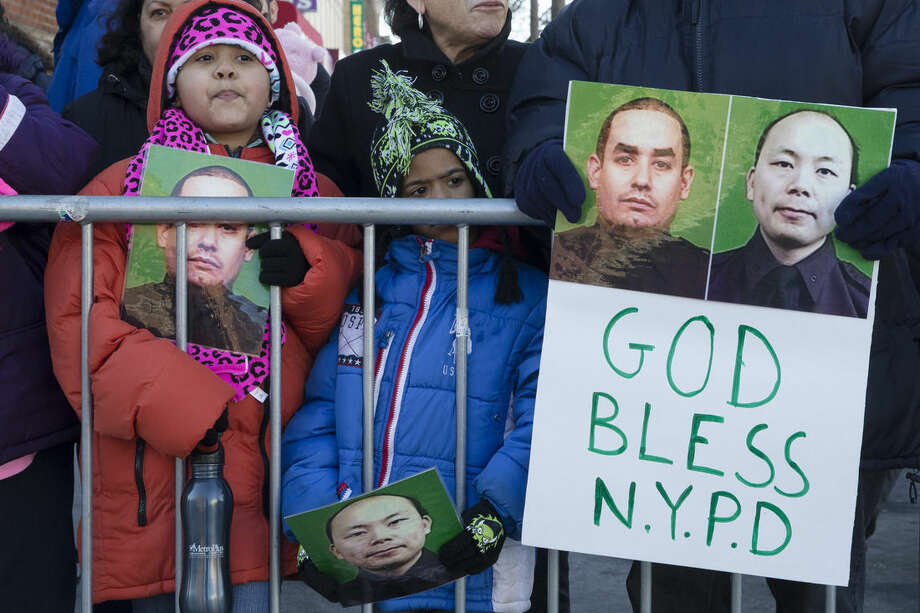Mourners stand at a barricade near Christ Tabernacle Church, in the Glendale section of Queens, as the casket of New York Police Department officer Rafael Ramos arrives for his wake, Friday, Dec. 26, 2014, in New York. Ramos was killed Dec. 20 along with his partner, Officer Wenjian Liu, as they sat in their patrol car on a Brooklyn street. The shooter, Ismaaiyl Brinsley, later killed himself. (AP Photo/John Minchillo)
