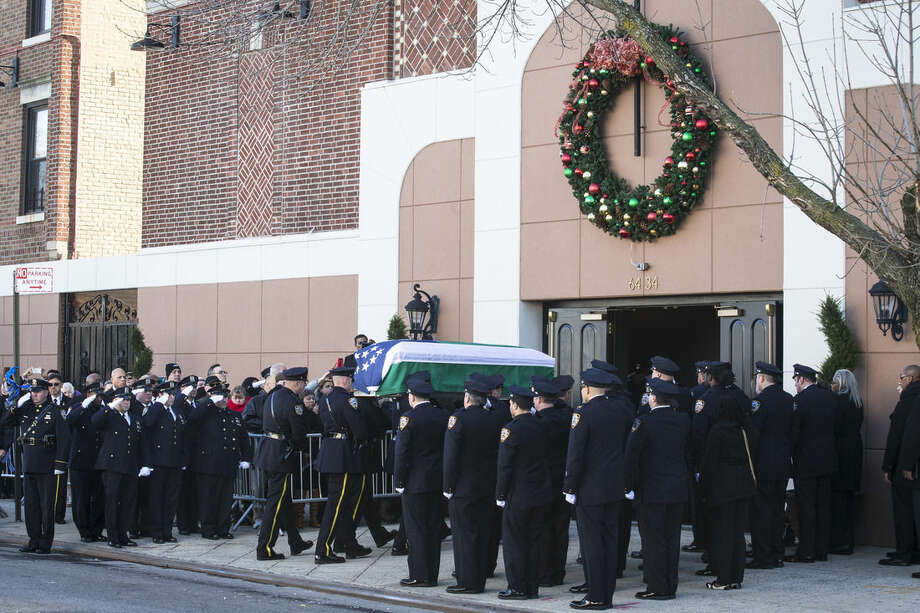 The casket of New York Police Department officer Rafael Ramos arrives to his wake at Christ Tabernacle Church, in the Glendale section of Queens, where he was member, Friday, Dec. 26, 2014, in New York. Ramos was killed Dec. 20 along with his partner, Officer Wenjian Liu, as they sat in their patrol car on a Brooklyn street. The shooter, Ismaaiyl Brinsley, later killed himself. (AP Photo/John Minchillo)