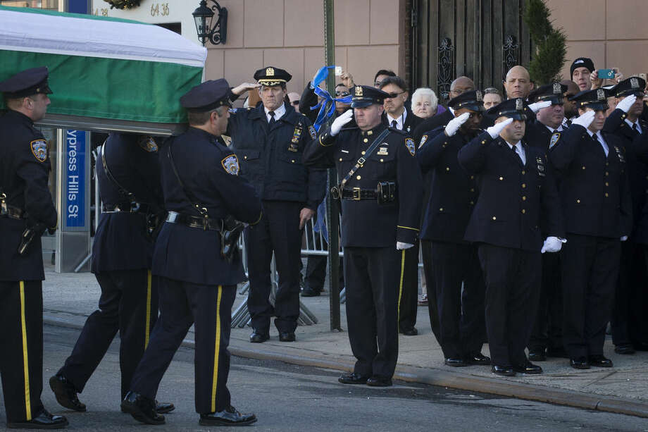 The casket of New York Police Department officer Rafael Ramos arrives to his wake at Christ Tabernacle Church in the Glendale section of Queens, where he was member, Friday, Dec. 26, 2014, in New York. Ramos was killed Dec. 20 along with his partner, Officer Wenjian Liu, as they sat in their patrol car on a Brooklyn street. The shooter, Ismaaiyl Brinsley, later killed himself. (AP Photo/John Minchillo)
