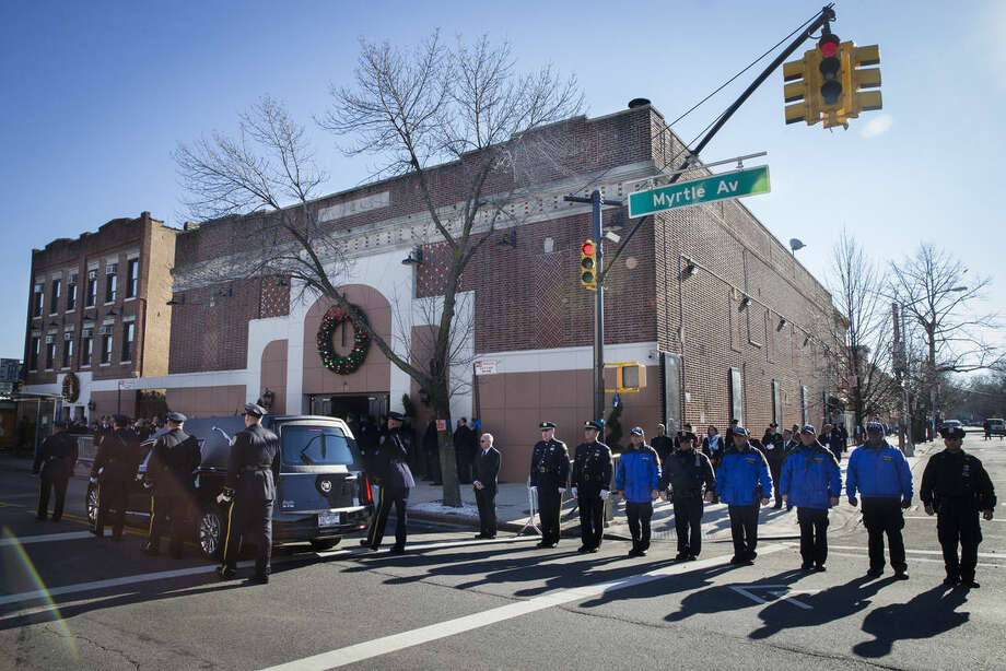 The casket of New York Police Department officer Rafael Ramos arrives to his wake at Christ Tabernacle Church, in the Glendale section of Queens, where he was member, Friday, Dec. 26, 2014, in New York. Ramos was killed Dec. 20 along with his partner, Officer Wenjian Liu, as they sat in their patrol car in Brooklyn. The shooter, Ismaaiyl Brinsley, later killed himself. (AP Photo/John Minchillo)