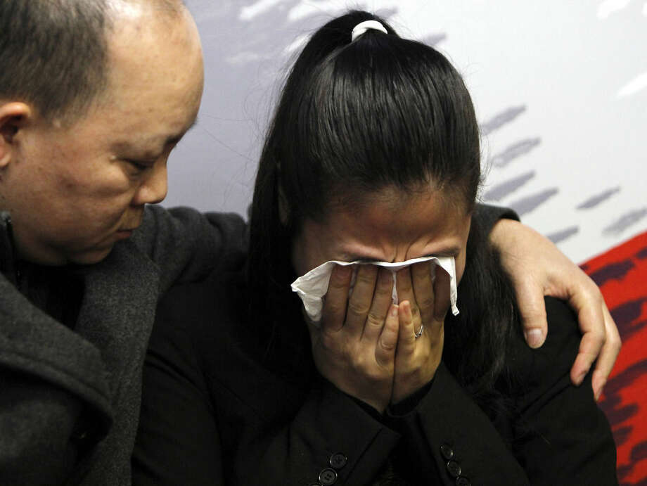 Pei Xia Chen, right, widow of slain New York City police officer Wenjian Liu, is comforted by family member Kevin Lee during a wake for New York City police officer Rafel Ramos, in the Queens borough of New York, Friday, Dec. 26, 2014. The Stephen Siller Tunnels to Towers Foundation announced they will raise money to pay off the home mortgages for the widows of Liu and Ramos. The officers were killed in Brooklyn by Ismaaiyl Brinsley on Saturday. (AP Photo/The Advance, Anthony DePrimo) NYC LOCALS OUT
