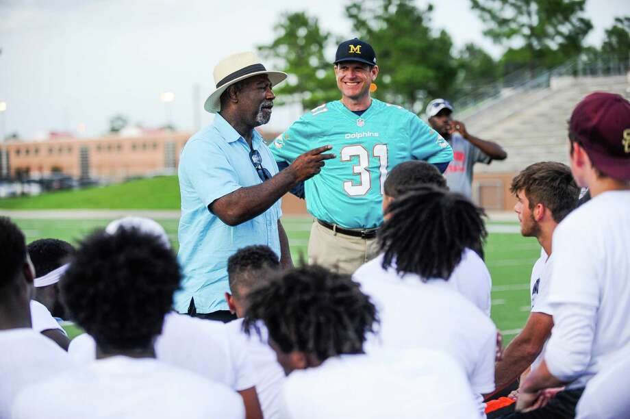 Head football coach at The University of Michigan Jim Harbaugh listens as Michael Thomas, father to the Dolphin's player Michael Thomas, talks to the athletes at the East Houston Elite Football Showcase Monday, June 13, 2016. His son, who played high school football in Texas was coached by Jim Harbaugh at Stanford. Photo: Erin Hull / Erin Hull