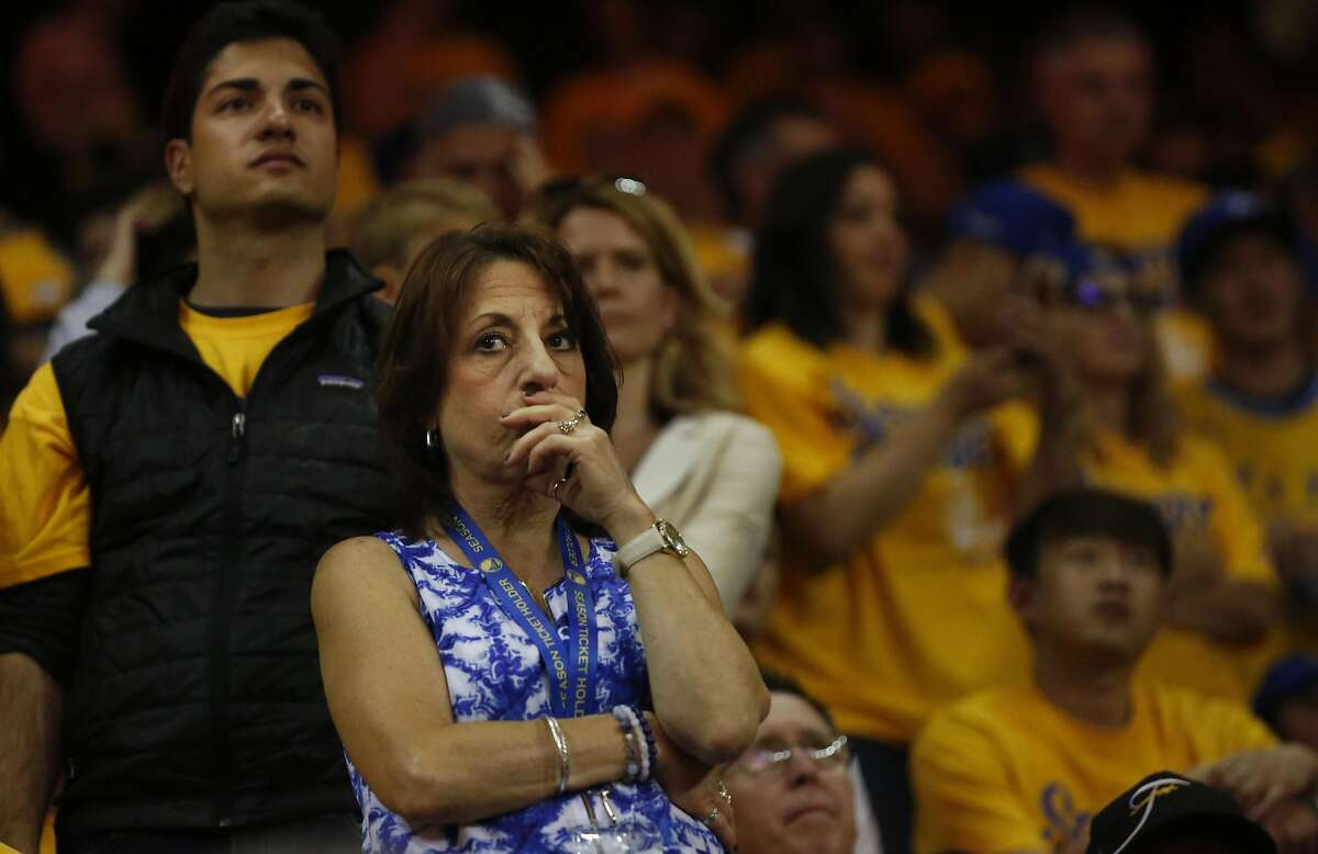 A fan watches the last quarter of Game 5 of the NBA finals between the Warriors and the Cavaliers at the Oracle Arena June 13, 2016 in Oakland, Calif.