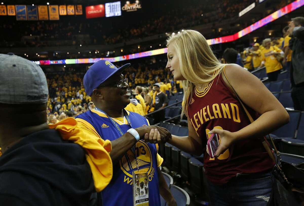 Bleacher Dave, left, shakes hands with Amanda Brady after joking around that it was her fault that the Warriors lost Game 5 of the NBA finals against the Cavaliers at the Oracle Arena June 13, 2016 in Oakland, Calif.