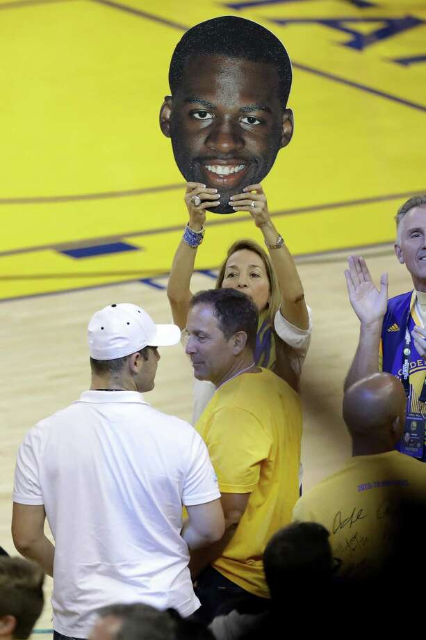 A Warriors fan holds up a likeness of the face of Draymond Green, who was suspended for Game 5 and watched the game next door at the Coliseum, where the A's played the Rangers. Photo: Ronald Martinez, Staff / 2016 Getty Images
