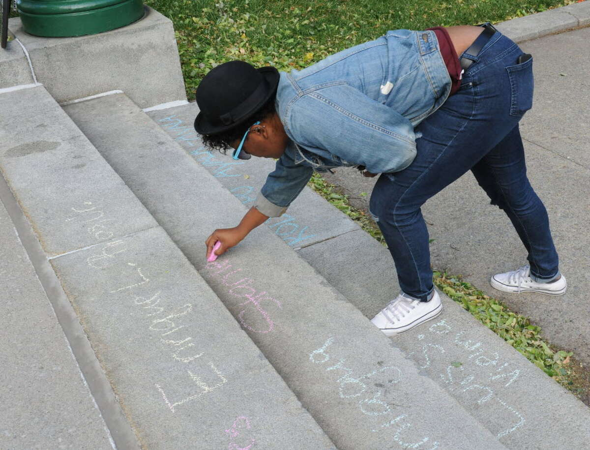 Deidre Dumpron of Albany uses chalk to write the names victims of the Orlando massacre during a vigil held at West Capitol Park on Monday, June 13, 2016 in Albany, N.Y. (Lori Van Buren / Times Union)