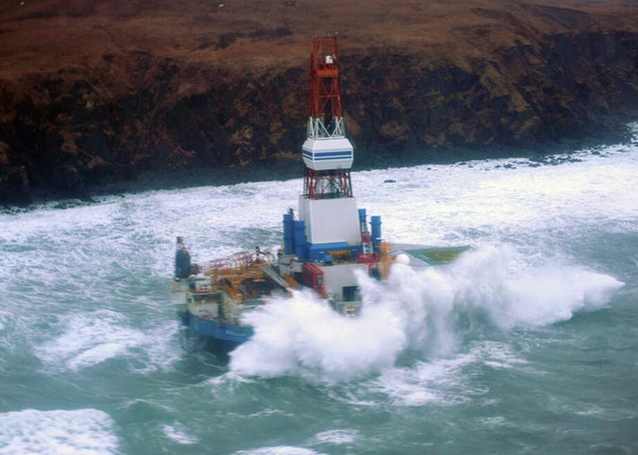 This image provided by the U.S. Coast Guard shows the Royal Dutch Shell drilling rig Kulluk aground off a small island near Kodiak Island Tuesday Jan. 1, 2013. A Coast Guard C-130 plane and a helicopter were used to fly over the grounded vessel on Tuesday morning. The severe weather did not permit putting the marine experts on board the drilling rig, which is near shore and being pounded by stormy seas. (AP Photo/U.S. Coast Guard) / US Coast Guard