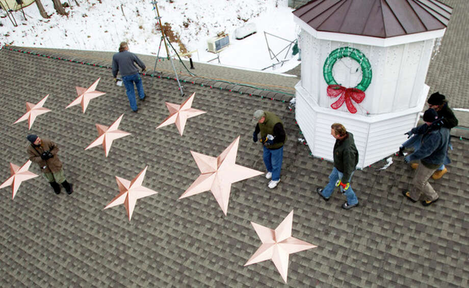 People work on the installation of 26 stars on the roof of the Sandy Hook fire station Tuesday, Jan. 1, 2013, in Newtown, Conn. The stars were made and installed by a group of local contractors, led by Greg Gnandt, to honor the memory of the victims of the Sandy Hook school shooting. (AP Photo/The News-Times, Brett Coomer) / Hearst Newspapers