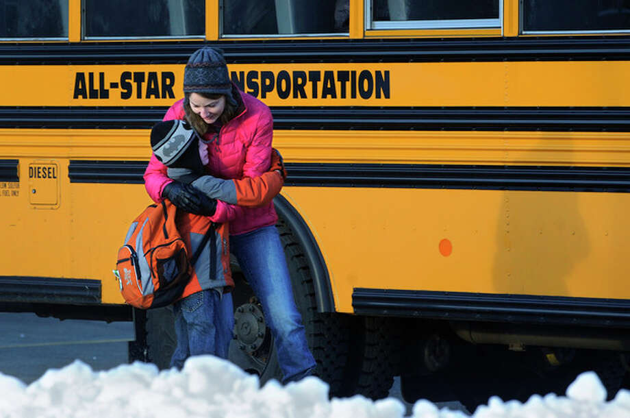 A woman hugs a child before he boards a bus on the first day of classes after the holiday break, in Newtown, Conn., Wednesday, Jan. 2, 2013. Children from Sandy Hook Elementary School will return to school Thursday in the neighboring town of Monroe. (AP Photo/Jessica Hill) / FR125654 AP
