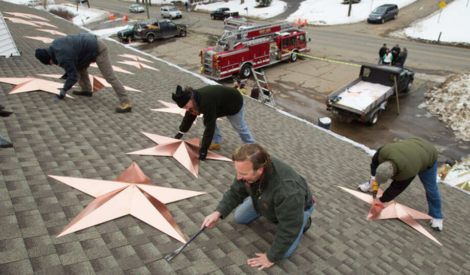 Volunteers, from left, Adrian Szepietowski, Guy Veneruso, Craig Schultz and Len Sabia, work on the installation of 26 stars on the roof of the Sandy Hook fire station Tuesday, Jan. 1, 2013, in Newtown, Conn. The stars were made and installed by a group of local contractors to honor the memory of the victims of the Sandy Hook school shooting. Nearly three weeks after the shooting rampage, classes are set to begin again for the Sandy Hook students Thursday, Jan. 3, 2013 at a repurposed school in the neighboring town of Monroe. (AP Photo/The News-Times, Brett Coomer) / The News-Times