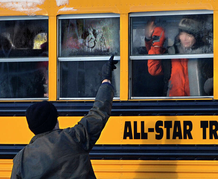 A man waves to a child on a bus on the first day of classes after the holiday break, in Newtown, Conn.,Wednesday, Jan. 2, 2013. Nearly three weeks after the shooting rampage at Sandy Hook Elementary School in Newtown, students and teachers from the school will return to class Thursday in the neighboring town of Monroe. (AP Photo/Jessica Hill) / FR125654 AP
