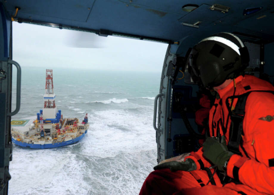 This aerial image provided by the U.S. Coast Guard shows Rear Adm. Thomas Ostebo, Incident Management Team commander, observing the Royal Dutch Shell drilling rig Kulluk aground during an overflight off a small island near Kodiak Island Tuesday Jan. 1, 2013. No leak has been seen from the drilling ship that grounded off the island during a storm, officials said Wednesday, as opponents criticized the growing race to explore the Arctic for energy resources. (AP Photo/U.S. Coast Guard, Sara Francis) / US Coast Guard