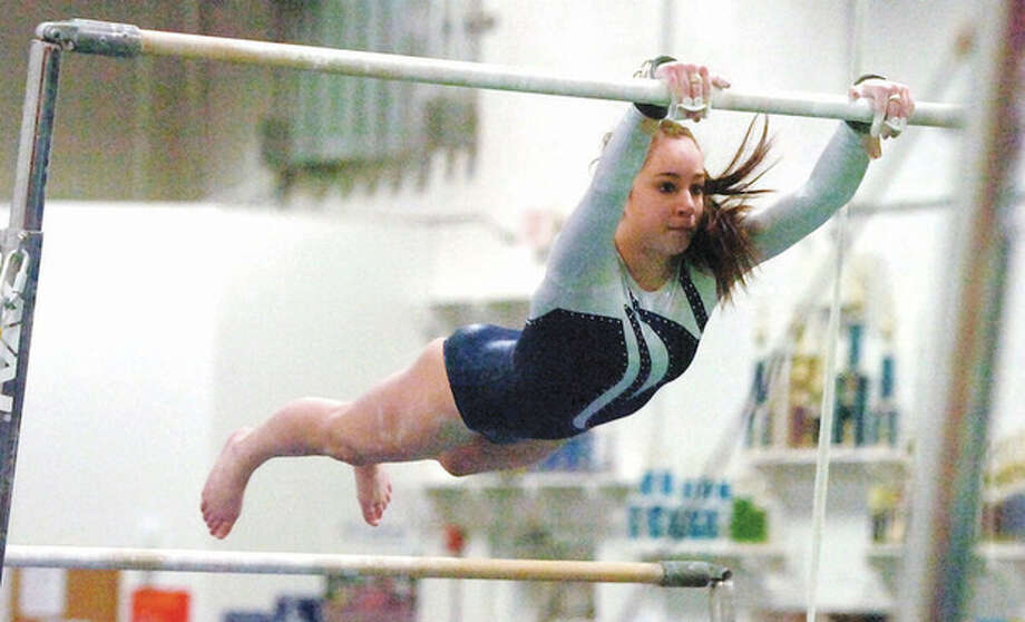 Hour photo/Alex von KleydorffWilton's Christina Brandt performs on the bars Wednesday during the Warriors' season-opening meet against Trumbull. The Warriors claimed a 131.85-129.20 victory over the Eagles. / 2013 The Hour Newspaper