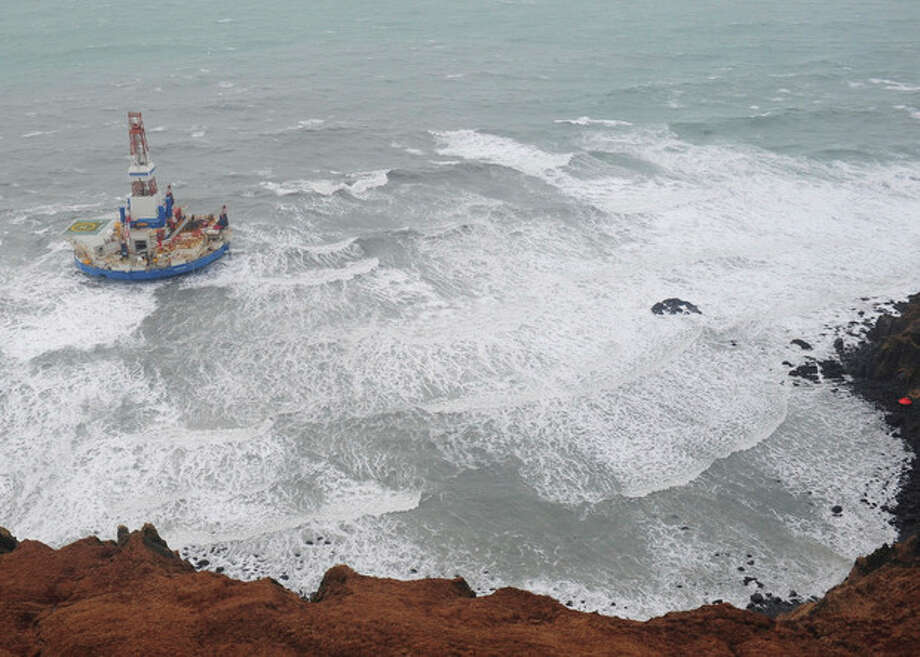 This aerial image provided by the U.S. Coast Guard shows the Royal Dutch Shell drilling rig Kulluk aground off a small island near Kodiak Island Tuesday Jan. 1, 2013. No leak has been seen from the drilling ship that grounded off the island during a storm, officials said Wednesday, as opponents criticized the growing race to explore the Arctic for energy resources. (AP Photo/U.S. Coast Guard) / US Coast Guard