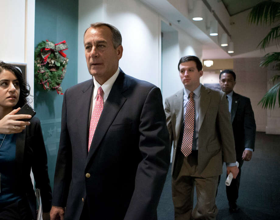 """Speaker of the House John Boehner, R-Ohio, walks to a closed-door GOP caucus as Congress meets to negotiate a legislative path to avoid the so-called """"fiscal cliff"""" of automatic tax increases and deep spending cuts that could kick in Jan. 1., at the Capitol in Washington, Sunday, Dec. 30, 2012. (AP Photo/J. Scott Applewhite) / AP"""